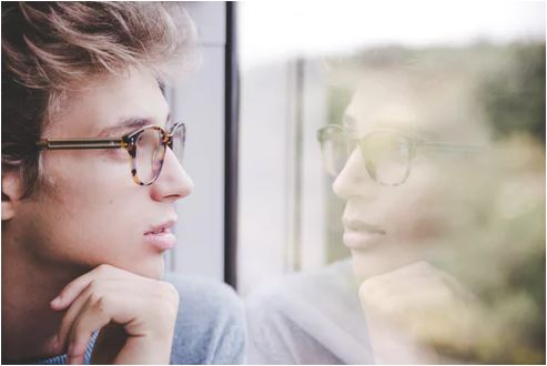 man looking out window and completing his daily reflection