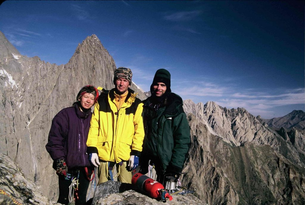 three people celebrate achievements on the summit of the central pyramid in kyrgyzstan
