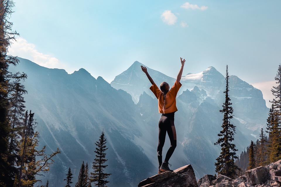 woman raises arms to celebrate achievements on summit of mountain