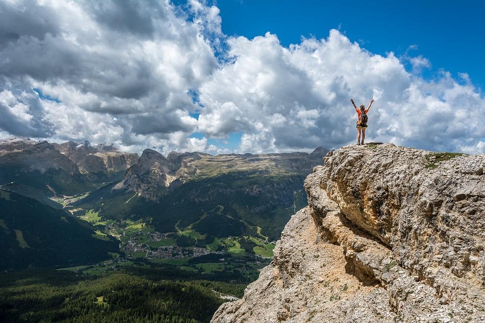 person on summit of mountain raises arms to celebrate achievement